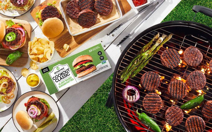 Hamburgers made with Beyond Burger from Beyond Meat are displayed cooking on a grill and complete on a table.