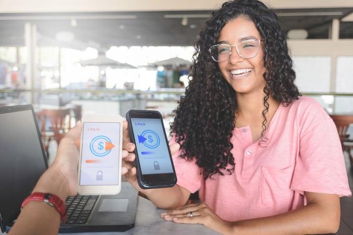 Deux personnes effectuent un transfert d'argent à l'aide d'une application pour smartphone.