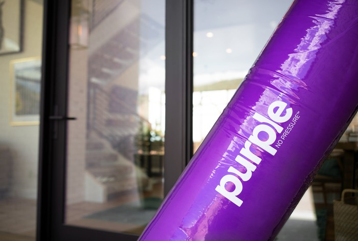 A rolled-up mattress from Purple Innovation sits outside someone's house.