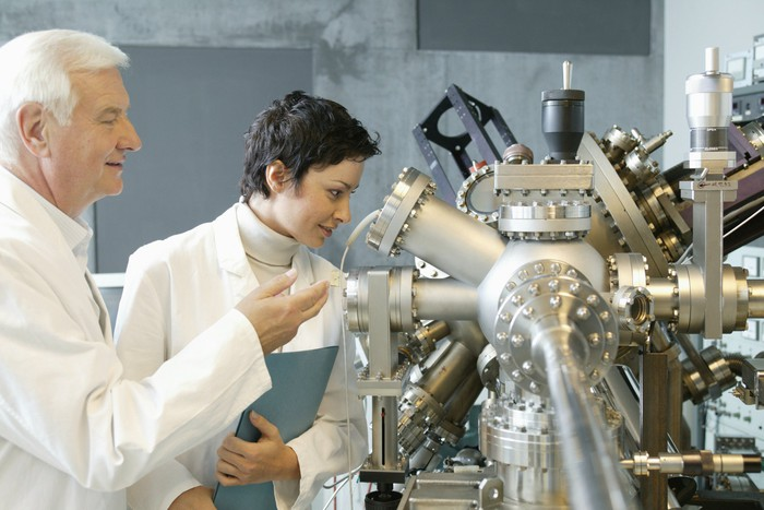 Two people observe manufacturing equipment.