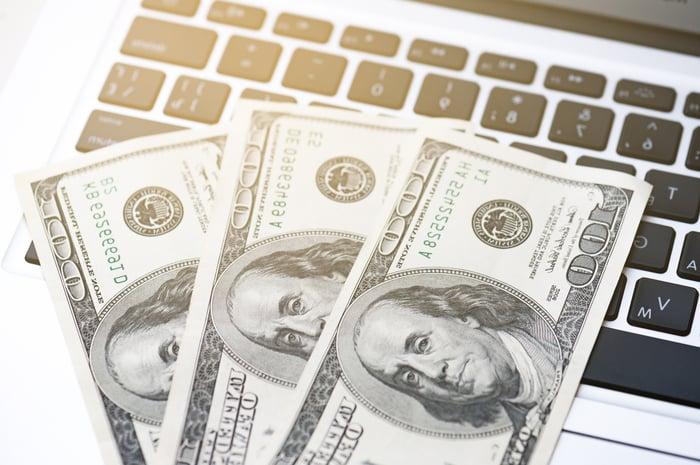 Three $100 bills on top of a laptop keyboard.