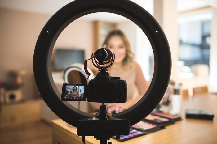 An internet personality speaks into a small camera in front of a ring light,.