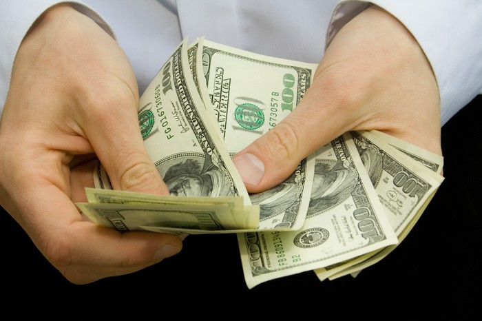 A mans hands counting a bunch of hundred dollar bills.
