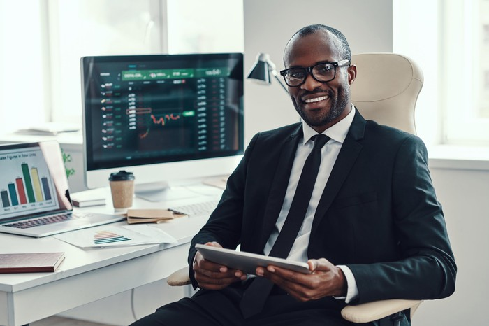 Man in suit looking at stock charts on computers