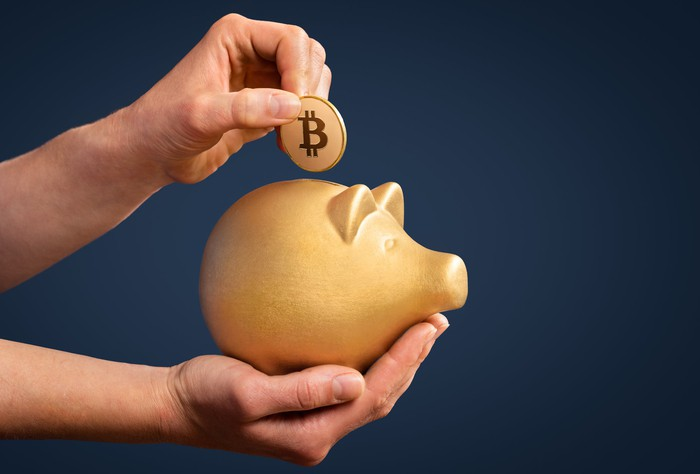 A hand drops a coin with the bitcoin symbol on it into a piggy bank.