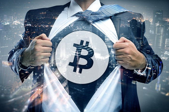 A suited man opens up his dress short to reveal a bitcoin symbol where a superhero symbol would be on his chest.