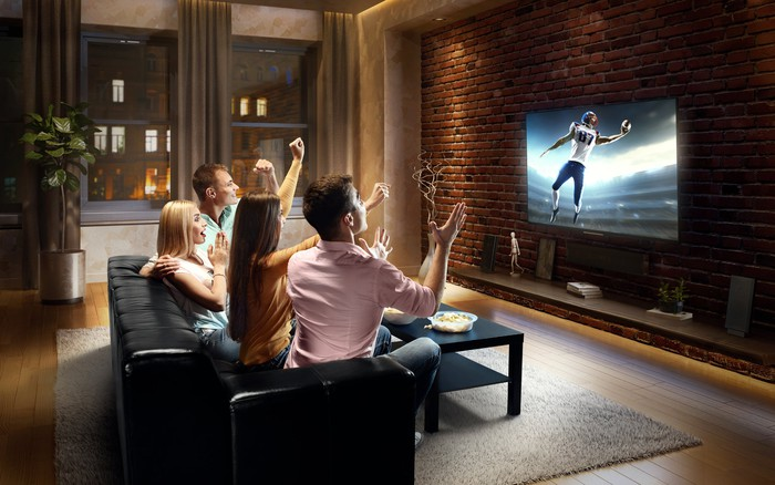 Two men and two women sitting on a couch and cheering as they watch a football game on a television