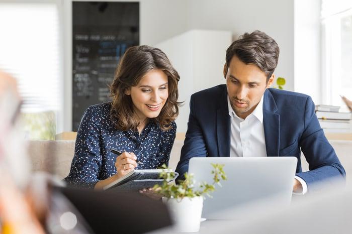 Un homme et une femme sont assis dans un café et travaillent sur un ordinateur portable.