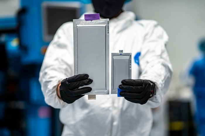 A worker in a white lab coat holds two rectangular silver battery cells, one larger than the other.