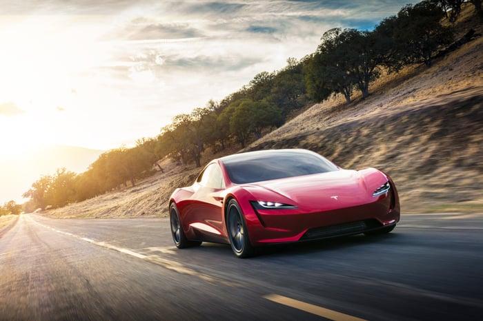 Red Tesla Roadster in motion.