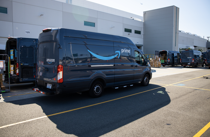 Amazon Prime delivery vans parked outside a large warehouse facility.