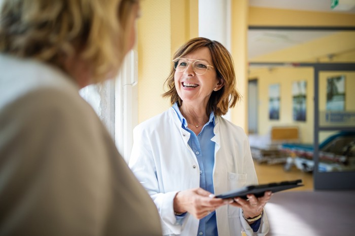 Female doctor holding a tablet discusses a matter with another person.