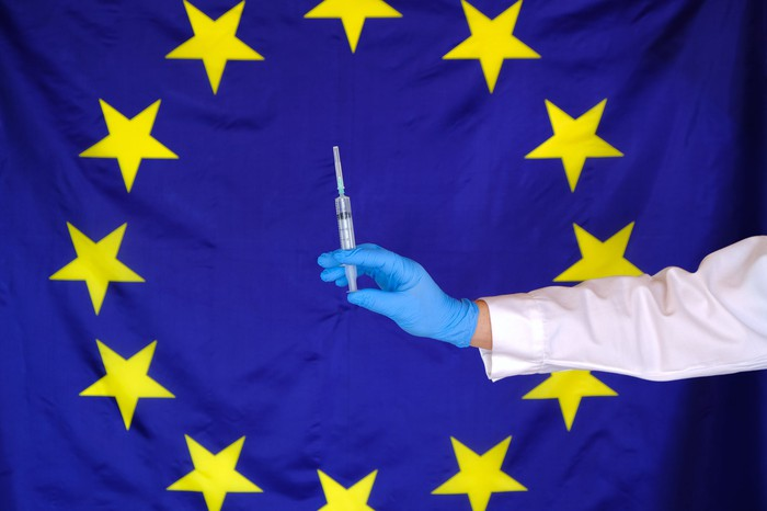 European Union flag with yellow stars in a circle on a blue background and a gloved hand holding a syringe with a needle in front of the flag