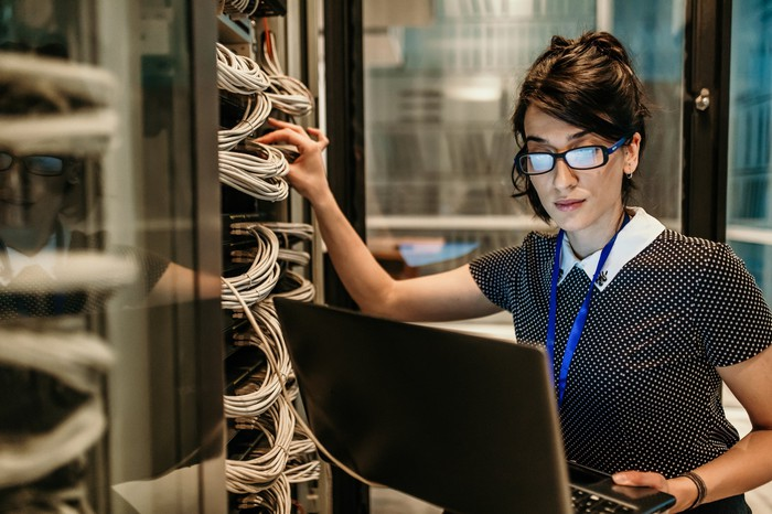 A woman holding computer server wires.