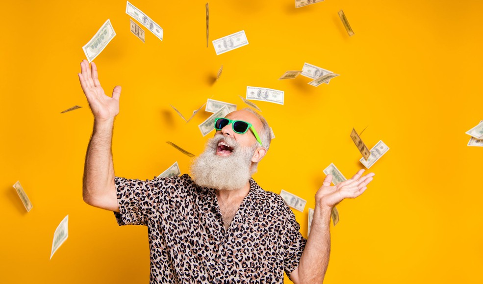 senior man wearing sunglasses throwing dollar bills in the air