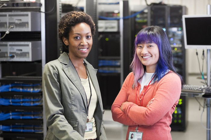 Two employees stand in front of rows of computer servers.
