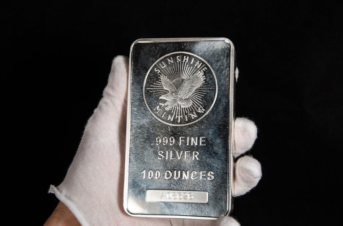 A gloved hand holding a silver bar weighing 100 ounces.