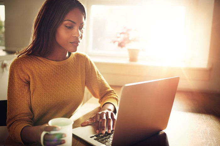 Woman with a cup of coffee sitting at a computer.