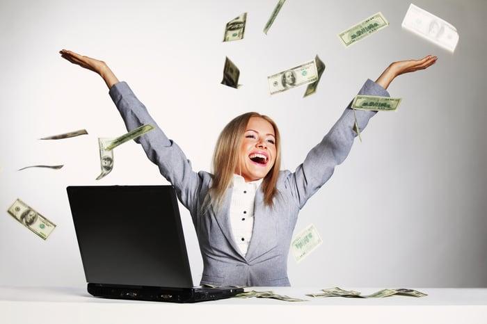 Une femme d'affaires souriante devant son ordinateur portable est entourée de billets de cent dollars tourbillonnant dans les airs.