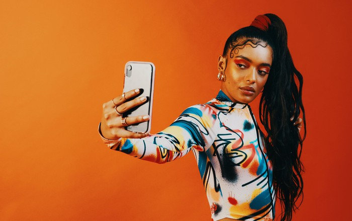 A fashionable young woman takes a selfie.