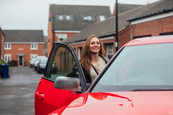woman getting into red ride-sharing car on London street