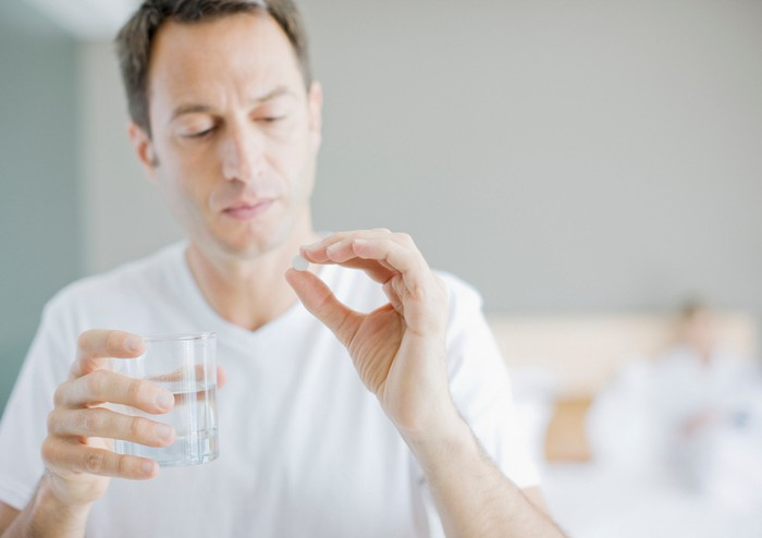 Person holds glass of water in one hand and a white pill in the other.