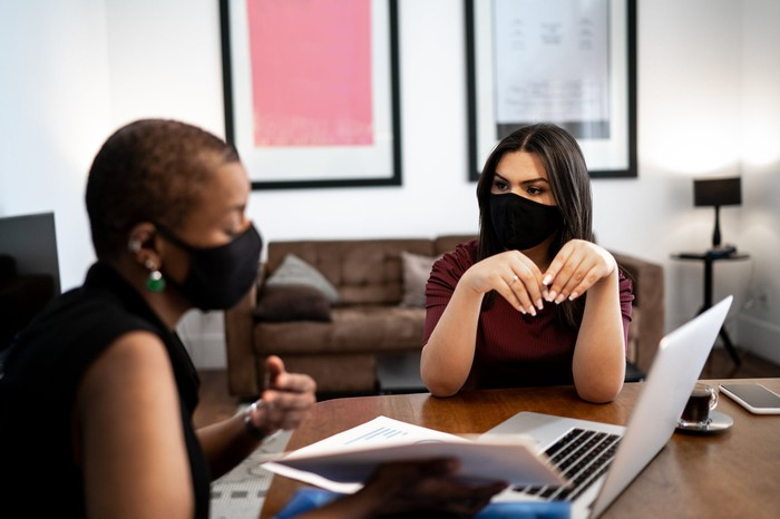 Two masked women talking while looking at a computer