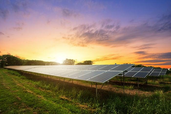 Solar farm in a field at sunset.