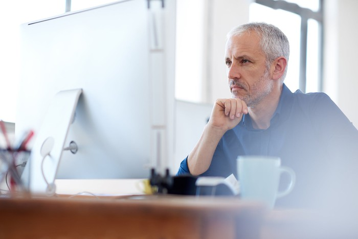 Man staring at laptop screen as if concentrating deeply