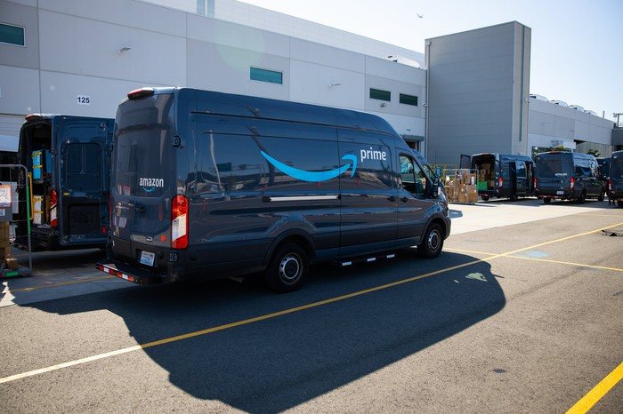 Amazon delivery vans parked outside a delivery station.