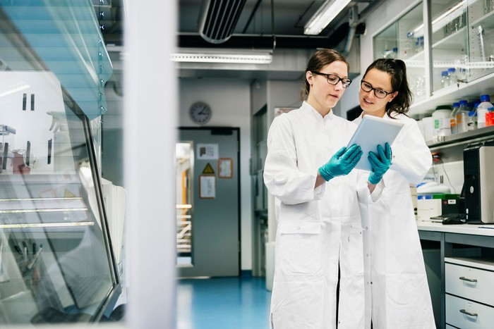 Two scientists wearing glasses, white coats, and gloves investigate data on a tablet in a lab setting.