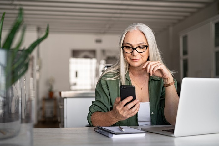 A woman checks her phone.