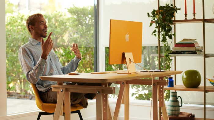 Man sitting in front of a new orange iMac.