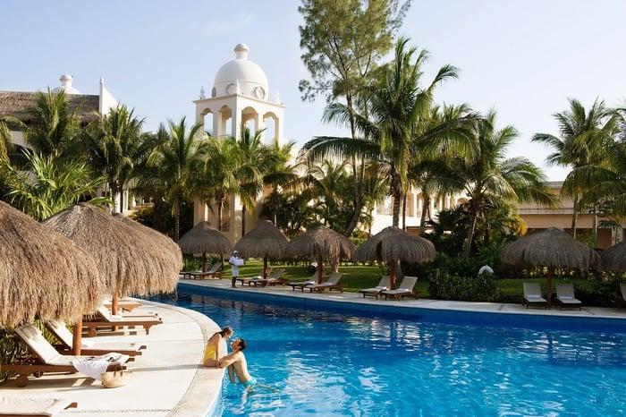 A couple enjoying a pool at a resort.