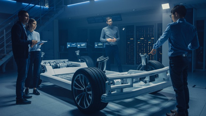 Engineers circle around an electric vehicle prototype.