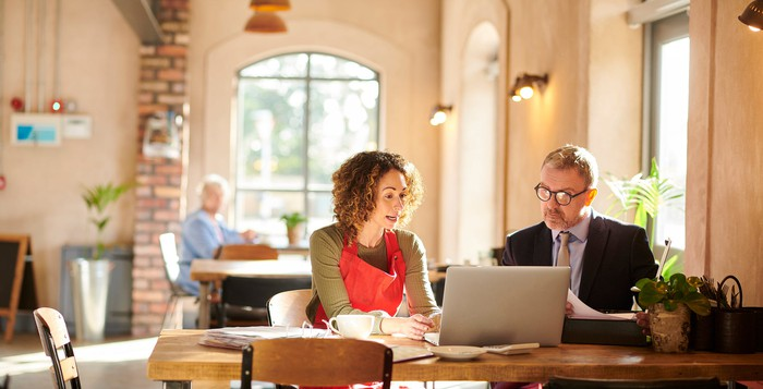 Banker advising small business owner in a coffee shop.