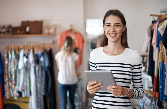 Woman holding tablet in clothes store