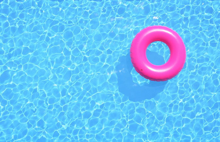 A pool toy floating in an empty pool.
