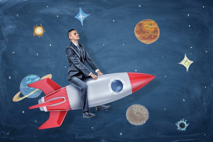Un homme d'affaires est assis sur une fusée devant un dessin d'arrière-plan d'étoiles et de planètes.