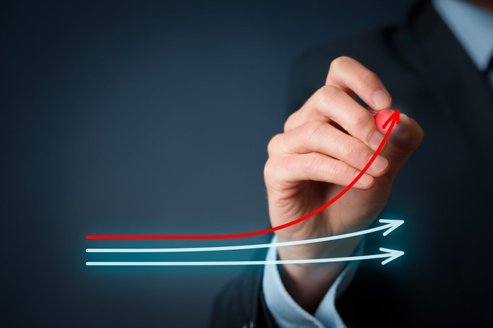 Man's hand drawing a rising red arrow above two blue arrows.
