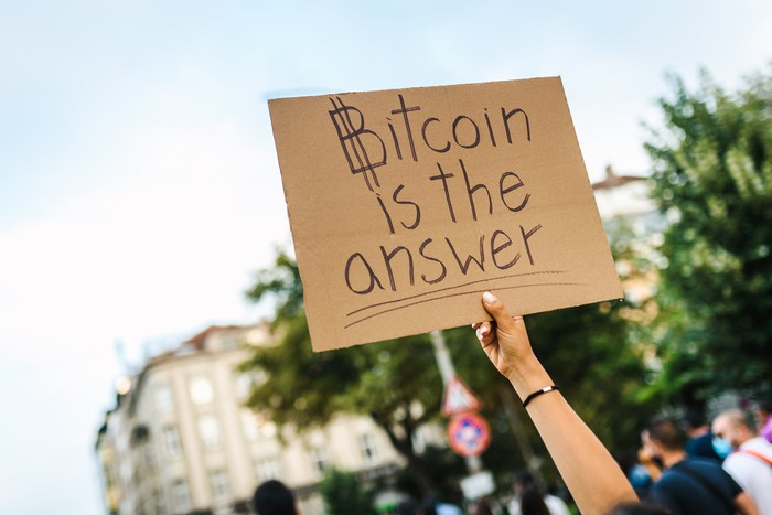 A person holding a cardboard sign up that reads, Bitcoin is the answer.