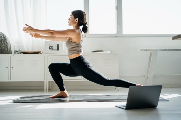 A woman does yoga in front of her laptop at home.