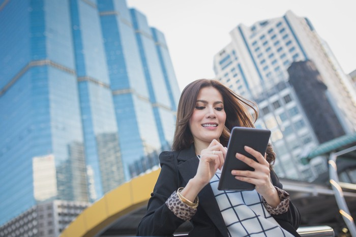 A woman smiles as she looks at a tablet while standing outside in a big city