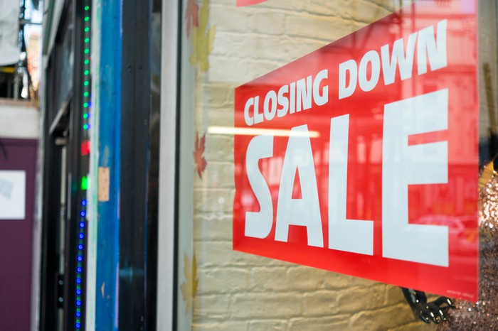 Red closing down sale sign hanging in a store window