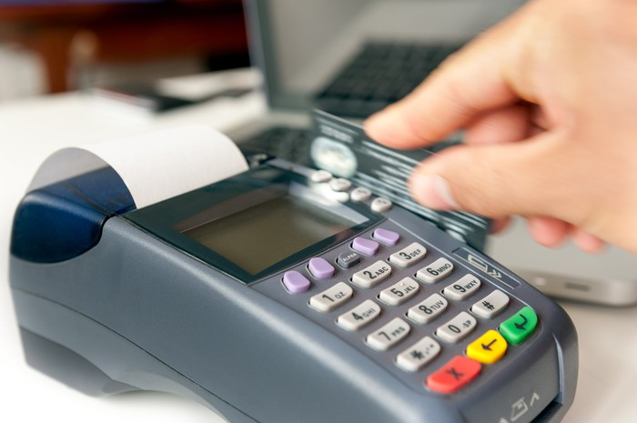 A hand swiping a credit card through a credit card machine.