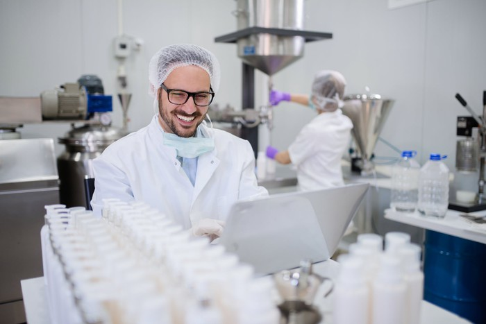 Smiling man in hairnet and lab coat, looking at a laptop inside a pharmaceutical lab