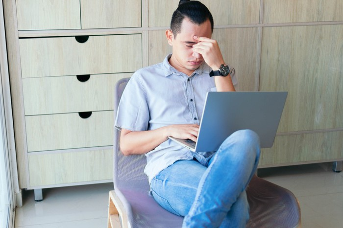 Rubbing his eyes, a man sits with a laptop on his lap.