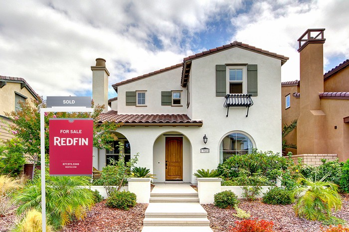 A Redfin for sale sign outside a house.