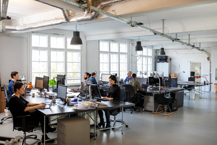 An industrial-style open concept office with many developers and engineers sitting at workstations.