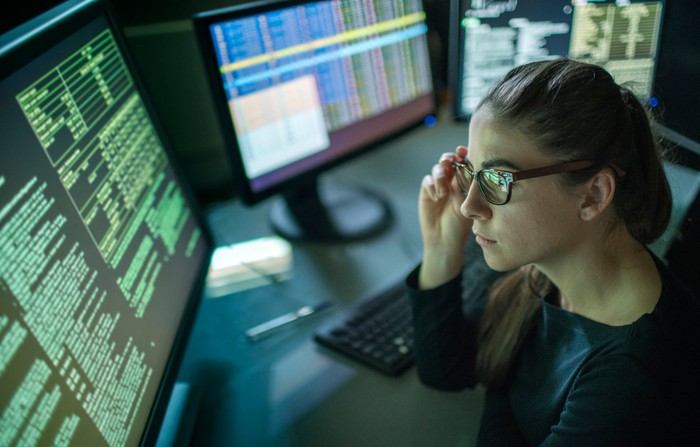 A young female tech worker looks at a large computer monitor with code running across.